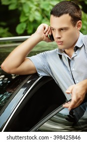 Portrait of young handsome dark-haired man about car speaking on mobile phone.