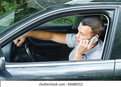 Portrait of young handsome dark-haired man driving car and speaking on mobile phone.