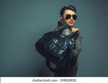 Portrait of young handsome fashion man with leather bag wearing sunglasses and leather jacket. Close up. Copy-space. Studio shot