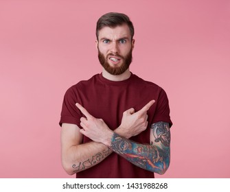 Portrait of young handsome frowning misunderstanding red bearded man in red t-shirt, stands over pink background looks at the camera with disgust and points in different directions.