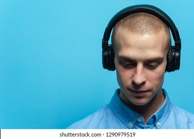 Portrait of a young handsome guy DJ in headphones and blue shirt posing against a blue background. Space for advertising