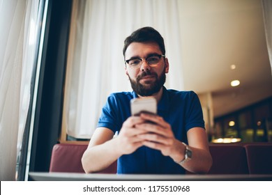 Portrait of young handsome hipster guy in spectacles for vision correction using modern mobile phone for typing message and looking at camera, milenial male holding smartphone for chatting on break