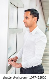 Portrait of Young Handsome Hispanic American Man in New York, wearing white shirt, standing by glass wall, looking outside, thinking, lost in thought. Side View.