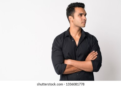 Portrait of young handsome Indian businessman thinking with arms crossed