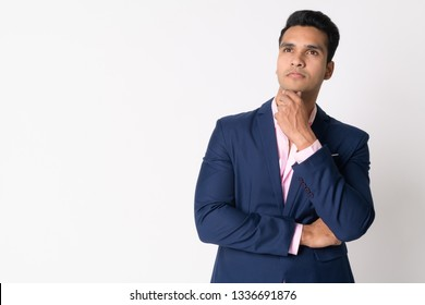 Portrait of young handsome Indian businessman in suit thinking