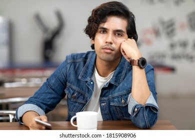 Portrait of a young handsome Indian man with serious look, lost in thought, sitting in an office cafeteria, coffee shop, casual work environment.