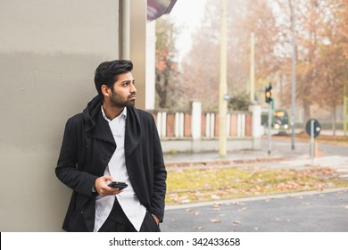 Portrait of a young handsome Indian man texting in an urban context