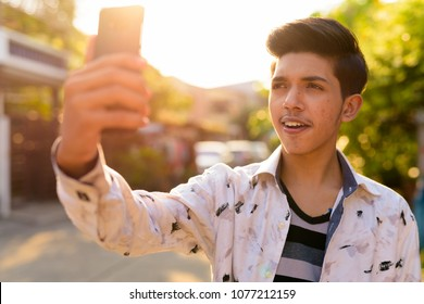 Portrait of young handsome Indian teenage boy in the streets outdoors