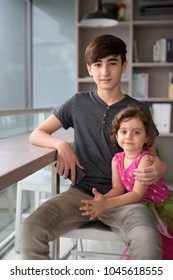 Portrait of young handsome Iranian teenage boy with little sister relaxing at home