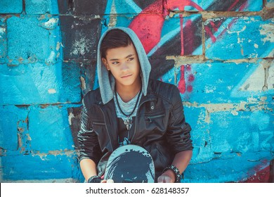 Portrait of a young handsome italian boy with skate and hood posing in the city urban graffiti background looking side wards