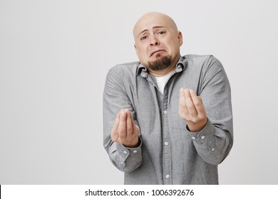 Portrait of young handsome man with a beard showing italian gesture that means what do you want over white background. Bald gloomy guy do not have clue of what happening and why his wife is shouting