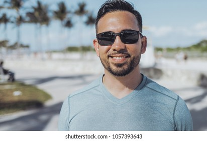 Portrait of young handsome man with beard wearing casual outfit and sunglasses looking at camera in park.