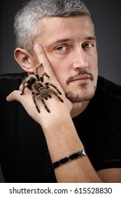 Portrait of a Young Handsome Man with Big Spider on His Hand.