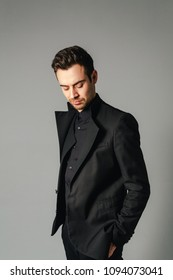 Portrait of a young handsome man in a black suit, standing and looking down, hand in pocket, against plain studio background