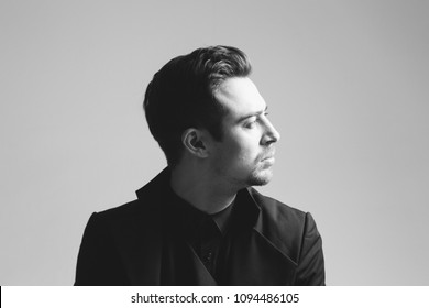Portrait of a young handsome man in a black suit, seriously looking to the side, against plain studio background