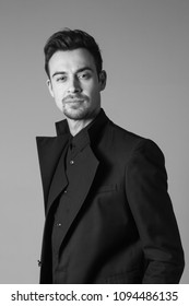Portrait of a young handsome man in a black suit, standing and seriously looking at the camera, against plain studio background