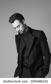 Portrait of a young handsome man in a black suit, standing and looking down, hands in pockets, against plain studio background