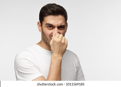 Portrait of young handsome man in casual clothes isolated on grey background holding his nose as if smelling something rotten and stinky looking aside trying to find source of odor
