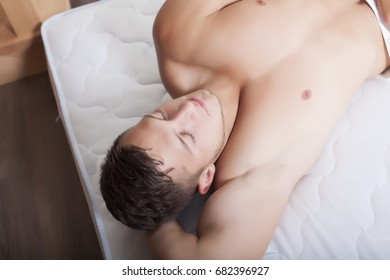 Portrait of young handsome man comfortably sleeping in bed at home