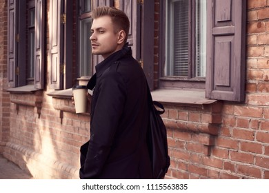 Portrait of young handsome man in dark coat with cup of coffee on old city background