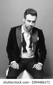 Portrait of a young handsome man in a dinner jacket,  sitting and seriously looking at the camera, against plain studio background.