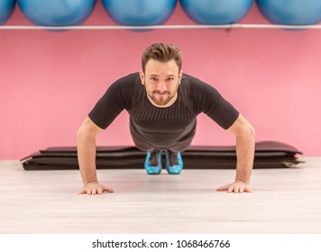 Portrait of a young handsome man doing pushups in a gym.