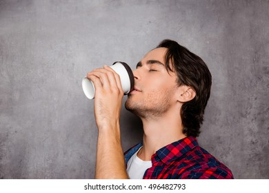 Portrait of young handsome man drinking coffee on gray background