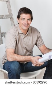 Portrait of young handsome man holding with blueprint