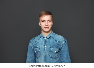 Portrait of young handsome man in jeans shirt looking at camera over dark grey background. Emotions and facial expressions concept.