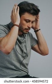Portrait of a young handsome man on a grayed background with headphones listening to music