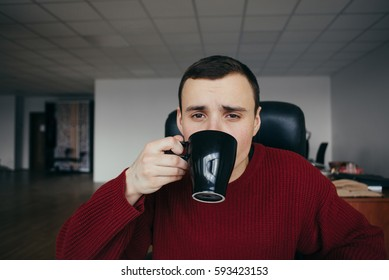 Portrait of a young handsome man sitting on workplace with cup of coffee in hand. Sleepy office worker