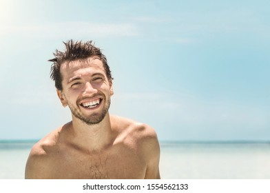 Portrait of young handsome man smiling at the camera on azure sea background