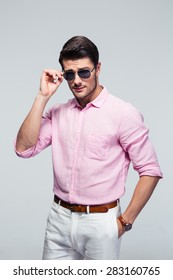 Portrait of a young handsome man in sunglasses over gray background