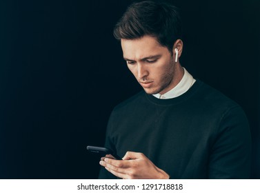 Portrait of young handsome man texting messages from his smart phone against studio black background, with wireless earphones. Caucasian businessman using wireless headphones