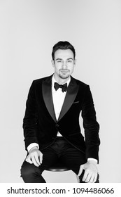 Portrait of a young handsome man in a tuxedo,  looking at the camera, against plain studio background.