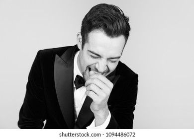 Portrait of a young handsome man in a tuxedo,  laughing, holding hand near face, against plain studio background.