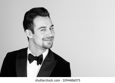 Portrait of a young handsome man in a tuxedo,  smiling and looking at the camera, against plain studio background.