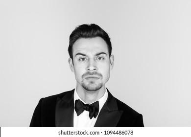 Portrait of a young handsome man in a tuxedo,  seriously looking at the camera, against plain studio background.