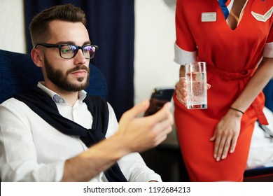 Portrait of young handsome man using smartphone with flight attendant bringing him drinks in background, copy space