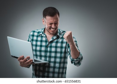 Portrait of young handsome man using laptop, wearing plaid shirt