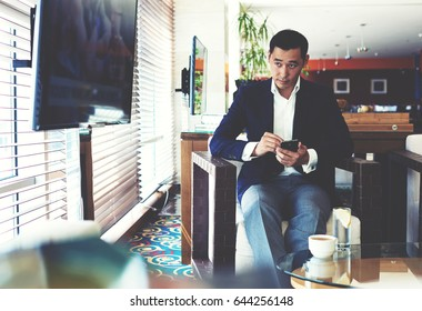 Portrait of a young handsome man watching the news on television during work on his mobile phone, successful managing director using cell telephone during coffee break in modern cafe inside