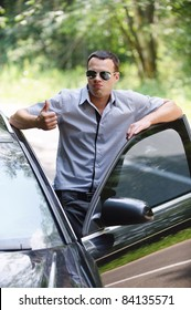 Portrait of young handsome man wearing sunglasses and showing thumbs-up gesture, standing near car.