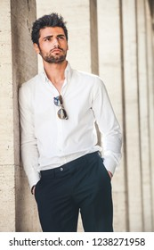 Portrait of young handsome man in white shirt outdoor. Nice appearance with stylish hair and beard. Leaning with a side on a wall