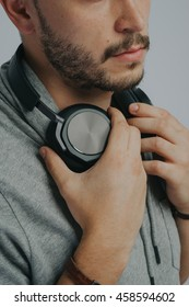 Portrait of a young handsome man's face on a grayed background with headphones listening to music