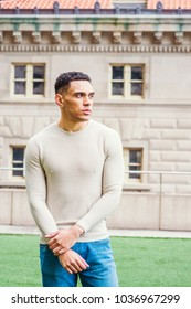 Portrait of Young Handsome Mixed Race Man in New York, wearing collarless knit pullover sweater, standing on green lawn outside office, looking forward,