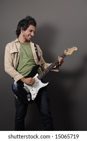Portrait of young handsome musician playing electric guitar
