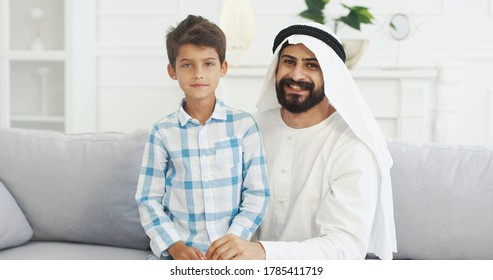 Portrait of young handsome muslim father in kandura sitting on couch in living room with cute small son, talking, giving five to each other and smiling to camera. Dad with little boy on sofa at home.