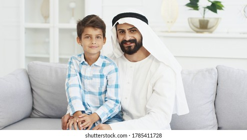 Portrait of young handsome muslim father in kandura sitting on couch in living room with cute small son on laps, talking, waving with hands and smiling to camera. Dad with little boy on sofa at home.