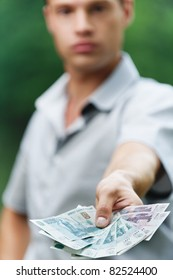 Portrait of young handsome serious man giving money at summer green park.