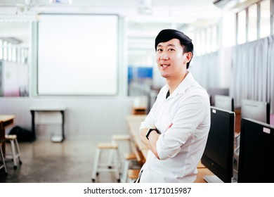 Portrait of young handsome smiling Asian male teacher in computer lab classroom background